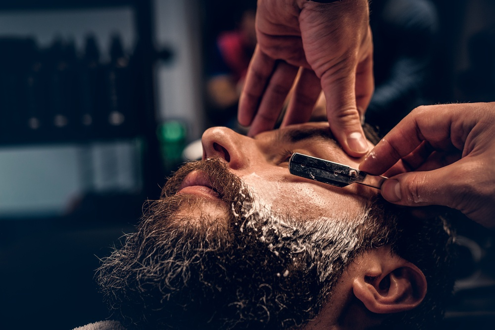 Man with long beard getting straight shave