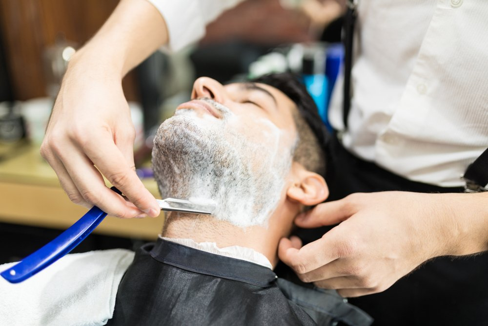 Man with stubble getting straight shave
