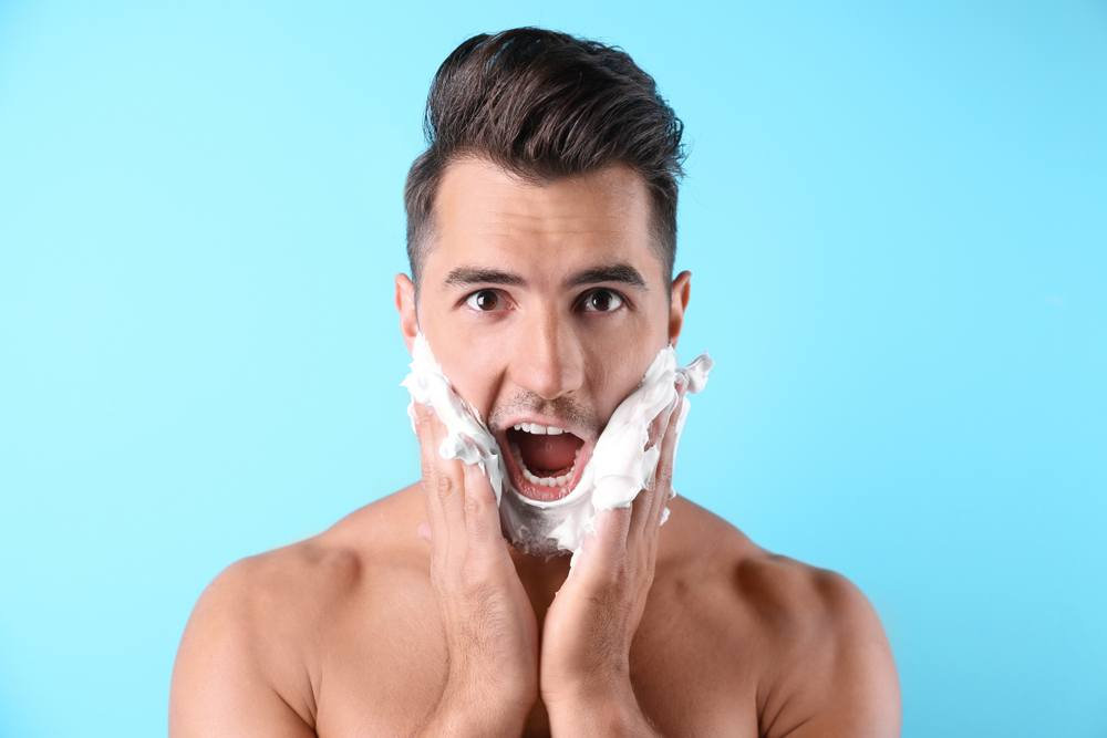 Man with hands on his face with shaving foams