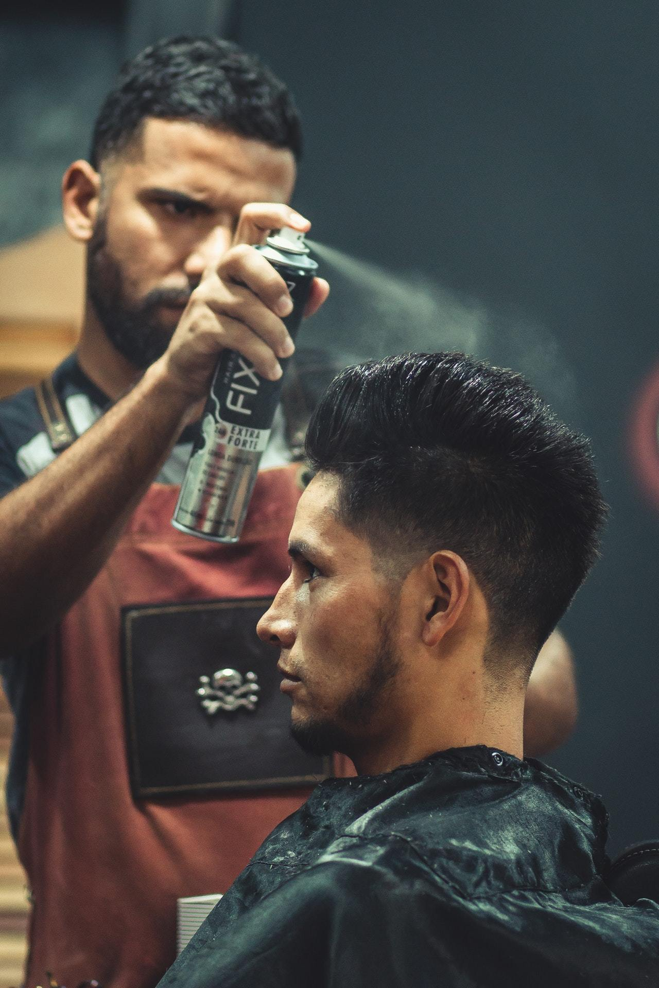 a man spraying hair / beard thickener sprays