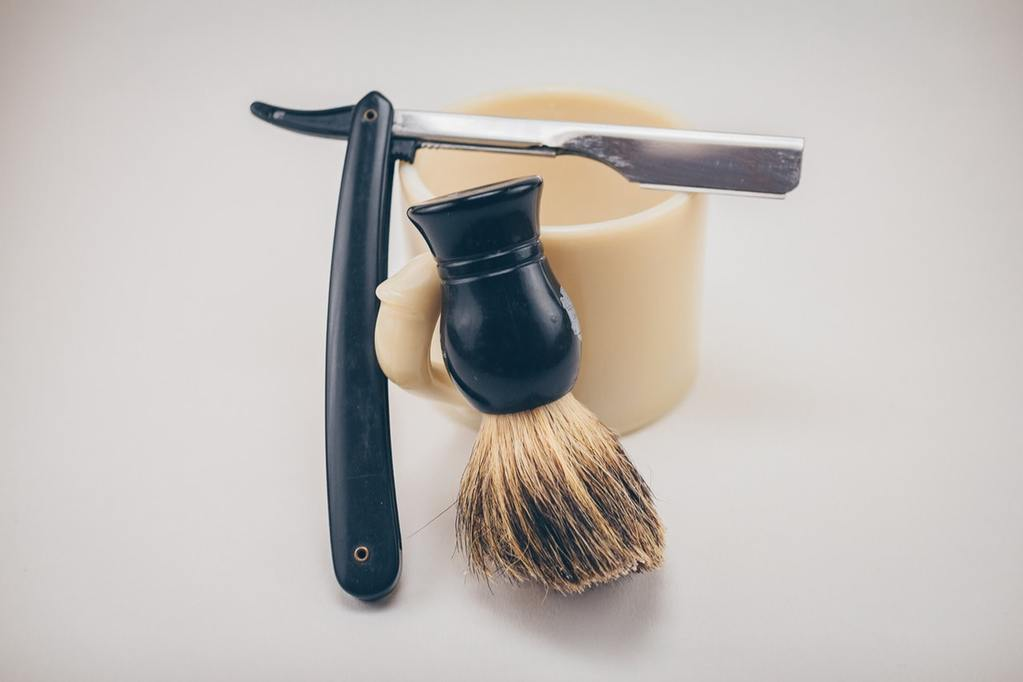 a shaving razor, brush, and cup