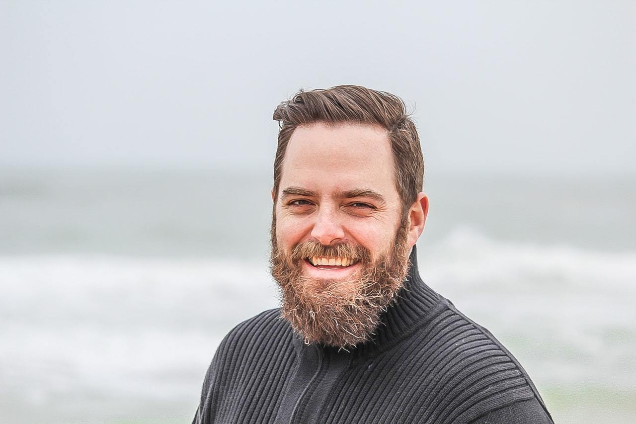 man wearing black zip up jacket near beach smiling at the camera